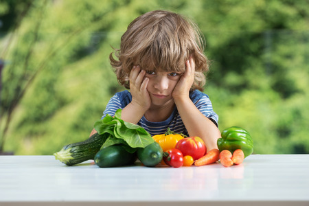 Cute little boy sitting at the table, frustrated by his vegetable meal, bad eating habits, nutrition and healthy eating concept