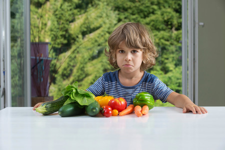 eating habits: Cute little boy sitting at the table, unhappy with his vegetable meal, bad eating habits, nutrition and healthy eating concept Stock Photo