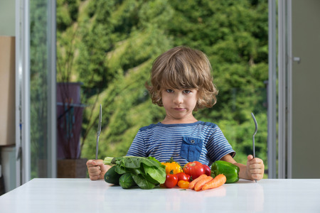 eating habits: Cute little boy sitting at the table, frowning over vegetable meal, bad eating habits, nutrition and healthy eating concept