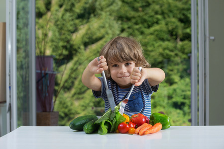 Cute little boy sitting at the table excited about vegetable meal, bad or good eating habits, nutrition and healthy eating concept Stockfoto
