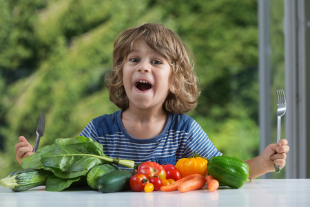 good and bad: Cute little boy sitting at the table excited about vegetable meal, bad or good eating habits, nutrition and healthy eating, showing emotions concept