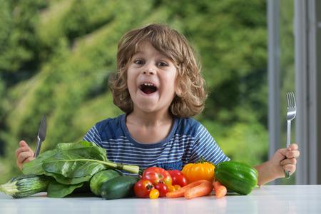comiendo: Niño pequeño lindo que se sienta en la mesa entusiasmado con comida vegetal, malos o buenos hábitos de alimentación, la nutrición y la alimentación saludable, mostrando concepto de las emociones