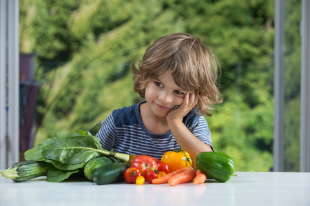 eating habits: Cute little boy sitting at the table excited about vegetable meal, bad or good eating habits, nutrition and healthy eating concept Stock Photo