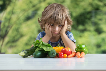 Cute little boy sitting at the table, frustrated by vegetable meal, bad eating habits, nutrition and healthy eating concept