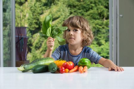 eating habits: Cute little boy sitting at the table, expressing mixed emotions over vegetable meal, bad eating habits, nutrition and healthy eating concept