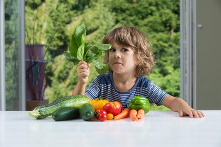 Netter kleiner Junge sitzt am Tisch, mit dem Ausdruck gemischte Gefühle über Gemüsemahlzeit, schlechte Ernährungsgewohnheiten, Ernährung und gesunde Ernährung Konzept Standard-Bild - 44118513