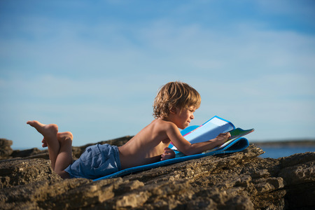 Cute little boy lying on his stomach looking at the picture book on the beach. Somen negative space around.