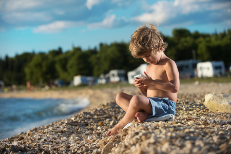 modern generation: Cute little boy playing with his smart phone on the beach. Modern lifestyle, modern generation concept.