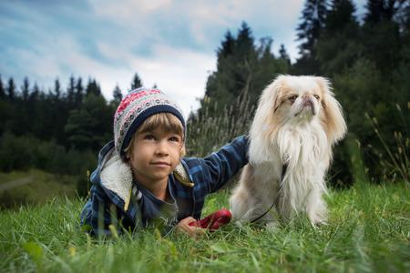 amigos abrazandose: Niño pequeño lindo que miente en la hierba junto a su perro. El mejor concepto amigos.