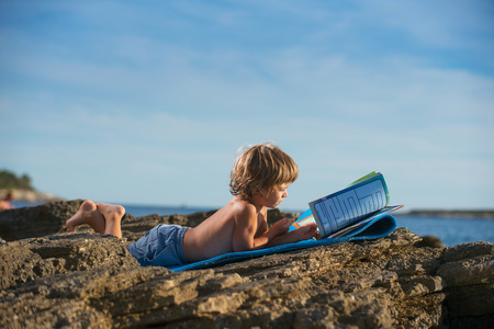Cute little boy lying on his stomach reading book on the beach. Some negative space around. Stockfoto
