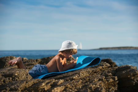 modern generation: Cute little boy with a cap lying on the beach playing with his smart phone. Modern lifestyle, modern generation concept.