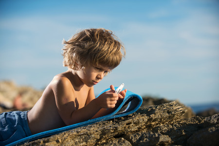 modern generation: Cute little boy lying on the beach playing with his smart phone. Modern lifestyle, modern generation concept.