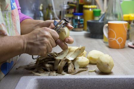 basura: Mujer pelando patatas en la cocina al lado del lavabo. Restos orgánicos, desechos de vegetales listos para el reciclaje y el compostaje. Comportamiento ambientalmente responsable.