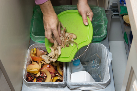 composting: Household waste sorting and recycling kitchen bins in the drawer. Collecting food leftovers for composting. Environmentally responsible behavior, ecology concept.