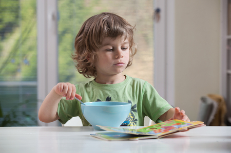 playing with spoon: Little boy reading book during his meal. Bad behavior, eating habbits concept