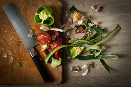 Organic leftovers ready for recycling and to compost, waste from vegetable on top of wooden chopping board with japanese usuba knife. Environmentally responsible behavior concept.