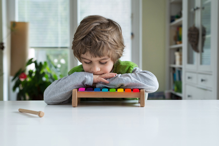 recognize: Cute little bored with playing on xylophone. Musical education, help recognize musical talent, how to support and encourage childrens creativity