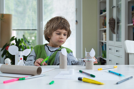 learning by doing: Little boy being creative making homemade diy paper toys. Supporting creativity, learning by doing, learning through experience. Helping child gain access to a creative way of seeing. Stock Photo