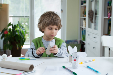 do: Little boy being creative making homemade diy paper toys. Supporting creativity, learning by doing, learning through experience. Helping child gain access to a creative way of seeing. Stock Photo