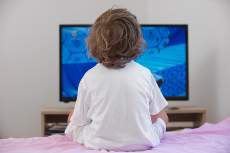 flat screen television: Little boy sitting on bed watching television.