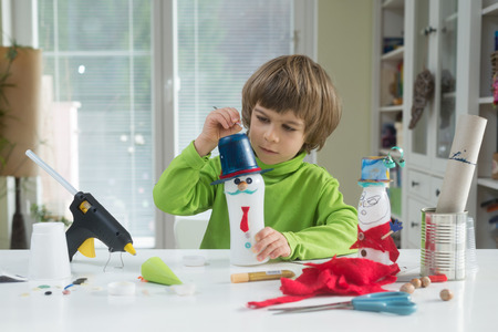 Little boy being creative making homemade do-it-yourself toys out of yogurt bottle and paper. Supporting creativity, hand craft. Helping child gain access to a creative way of seeing. Stockfoto