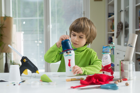 doityourself: Little boy being creative making homemade do-it-yourself toys out of yogurt bottle and paper. Supporting creativity, learning by doing, hand craft.