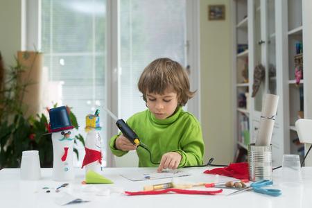 El niño pequeño es creativo haciendo juguetes caseros de bricolaje en una botella de yogurt y papel usando una pistola de pegamento termofusible. Apoyando la creatividad, manualidades.
