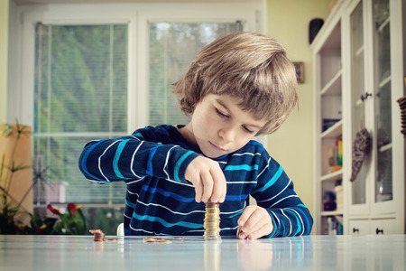 Little boy making stack of coins, counting money at table. Learning financial responsibility and planning savings concept. Archivio Fotografico