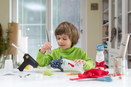 Kleine jongen die creatief schilderij stippen op zelfgemaakte doe-het-zelf speelgoed gemaakt van yoghurt fles en papier. Creativiteit ondersteunen, handwerk. Creatieve recreatie voor kinderen binnenshuis.