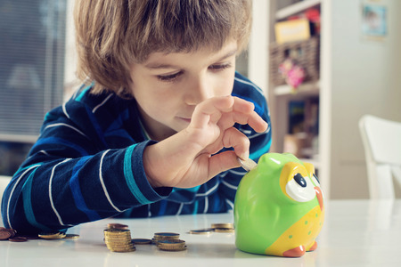 Little boy putting coins into owl piggy bank. Learning financial responsibility and projecting savings.