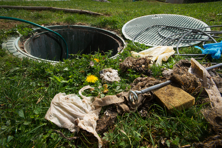 Unclogging septic system. Cleaning and unblocking drain full of disposable wipes and other non biodegradable items. Reklamní fotografie - 85683517