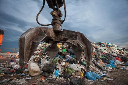 市の埋め立て地で山からの廃棄物をつかんでメカニカル アームのクローズ アップ