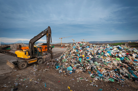 Bulldozer with mechanical arm grabbing waste from a pile at city landfill. Waste management, ecology concept. Stock Photo