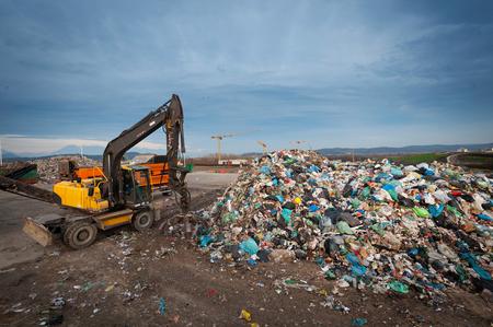Bulldozer con il braccio meccanico che afferra lo spreco da un mucchio alla discarica della città. Gestione dei rifiuti, concetto di ecologia.