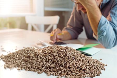 Mens die de verwarmingskosten van het huishouden berekent. Houten pellets, biomassa, effectieve, milieuvriendelijke en zuinige verwarming, duurzame en hernieuwbare energie Stockfoto