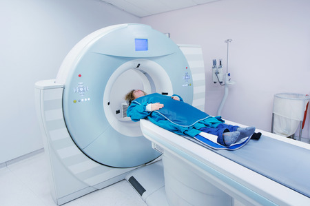 Female patient undergoing CT - Computerized Tomography Scan in Hospital. Patient wearing lead apron to   cover vital organs.