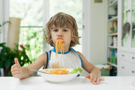 Portrait of a cute young boy making a mess while eating pasta for lunch