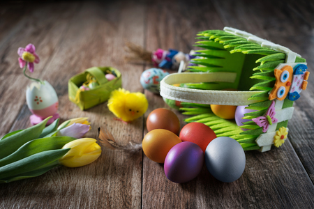 Easter decoration with eggs in a basket on wooden background.  스톡 콘텐츠