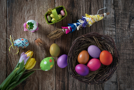 Easter decoration with tulips and eggs in a nest on wooden background.
