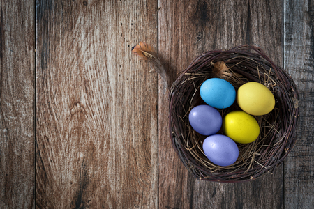 Easter eggs in nest on rustic wooden background. Some negative space left.