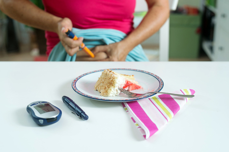 Female diabetic patient injecting herself with shot of insulin before having a piece of cake for desert.