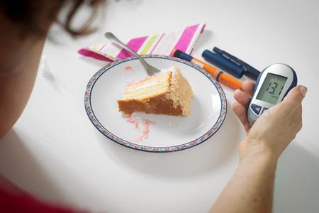 Female hand holding blood sugar meter next to plate of cake. Diabetes, high blood sugar, modern disease concept.