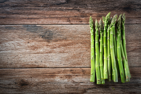 Bunch of fresh asparagus on wooden rustic background. Copy space