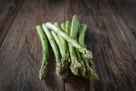 Closeup shot of fresh asparagus bunch on wooden rustic background