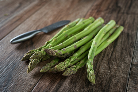 Closeup shot of fresh asparagus bunch with kitchen knife aside on wooden rustic background