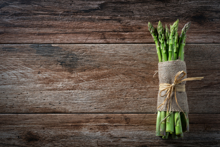 Bunch of fresh asparagus tied with a rope on wooden rustic background. Copy space.