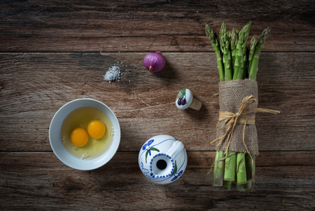 Bunch of fresh asparagus, with eggs, onion and salt on rustic wooden background. Ingredients ready to make a meal. Top view. Banco de Imagens