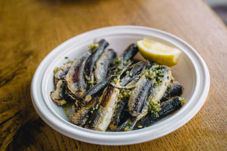 Plate of fried sardines with slice of lemon on wooden table. Mediterranean style fast food.