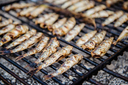 Fresh grilled sardines on grill. Close up, shallow depth of filed. Banco de Imagens