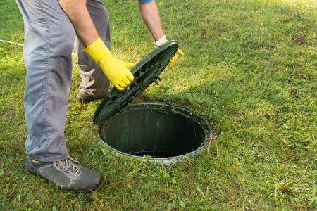 Opening septic tank deksel. Reinigen en ontstoppen van septisch systeem en afvoerleidingen.